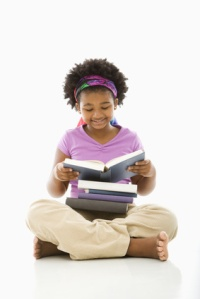 African American girl with large stack of books reading.